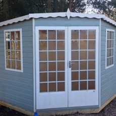 7 x 7 Shire Gold Windsor Corner Summerhouse - front view painted blue with white fascia windows and
