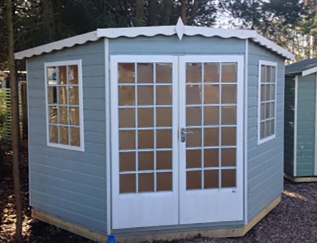 8 x 8  Shire Gold Windsor Corner Summerhouse - ront view painted blue with white fascia windows and